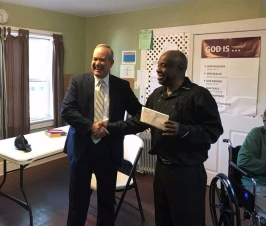 Rev Johnson receives a check from Fred Williams with Synovus Bank
